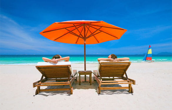 Couple on a tropical beach relax in the sun on deck chairs under a red umbrella travel