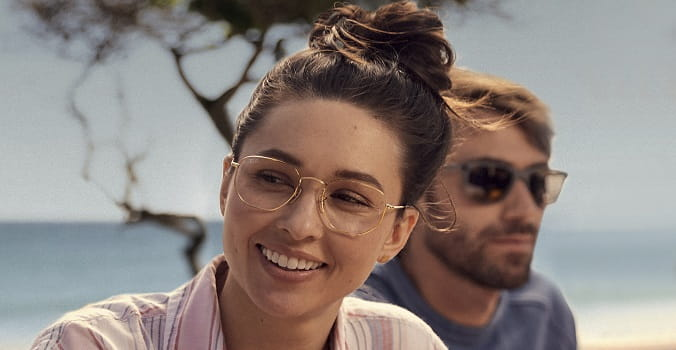 Woman at the beach wearing eyeglasses smiling with man with sunglasses in background