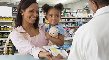 Mother and daughter handing a prescription to a Pharmacist