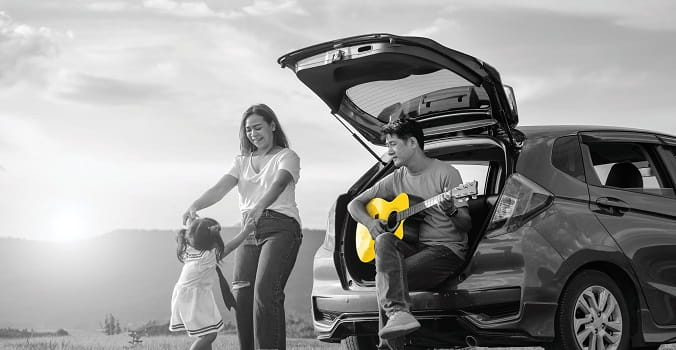 Dad playing guitar out of rear of a SUV with Mom and young daughter dancing in the sun