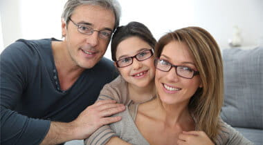 Family of three smiling wearing eyeglasses