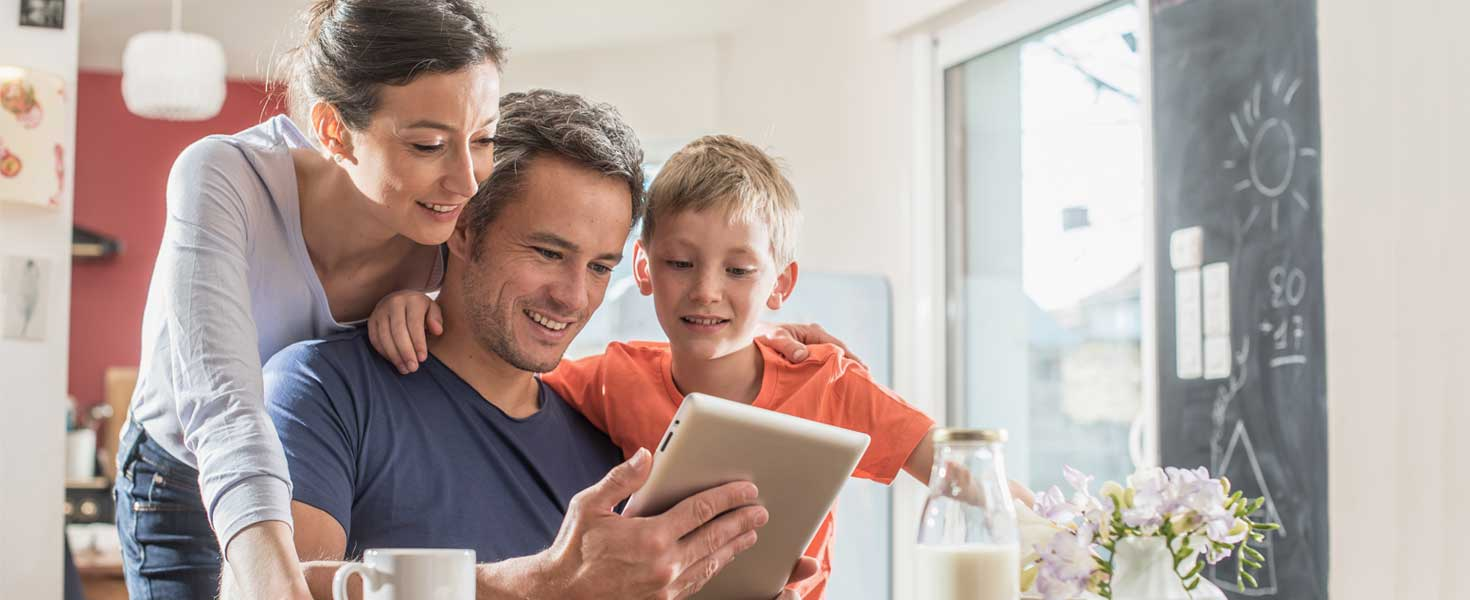 A modern family using a digital tablet while having breakfast in the kitchen, mom, dad and their eight year old son.