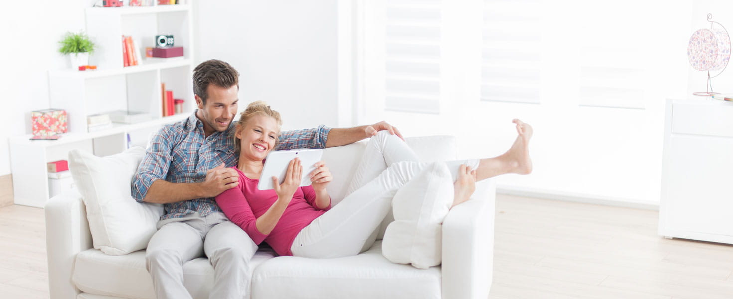Happy couple sitting on couch looking up member discounts online.