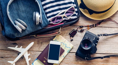 Clothes, Passport, wallet, glasses, smart phone devices, on a wooden floor in the luggage ready to travel