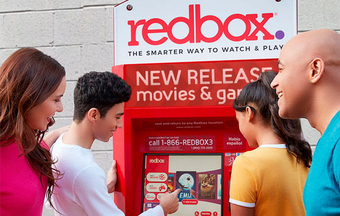 Family gathered around redbox station looking a movies to rent.