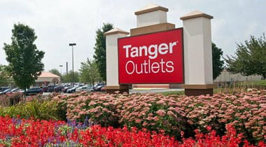 Tanger outlet sign surrounded by flowers