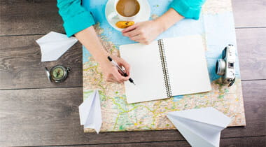 Overhead look of man with travel plans, cup of coffee, notepad, camera and map on a desk