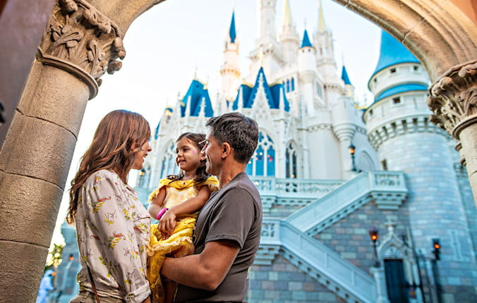 Family smiling and laughing standing outside of the Disney castle.