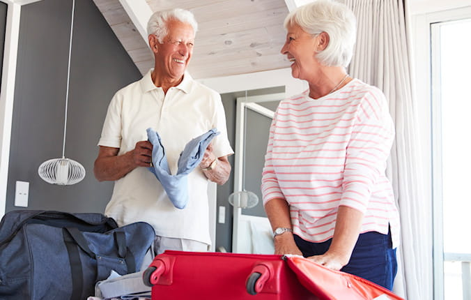 Couple laughing while they are packing their suitcase for their trip.