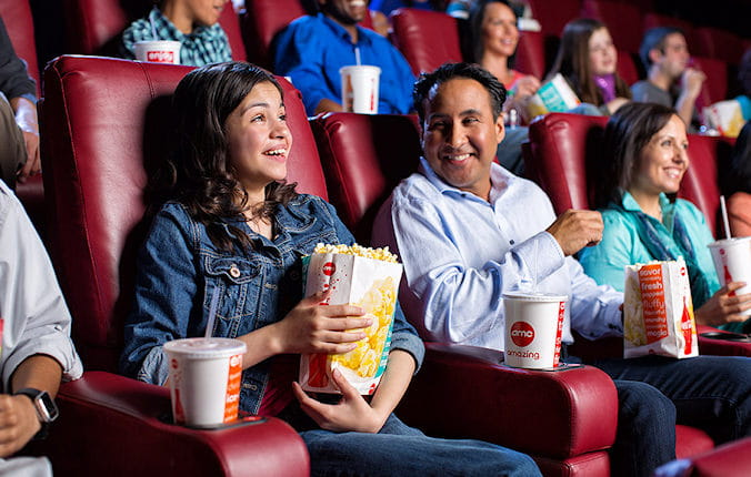 Young couple eating popcorn waiting for movie to start.