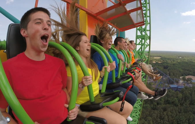 Group of friends yelling of excitement on roller coaster.