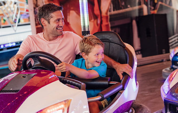 Father and sun laughing while riding bumper cars