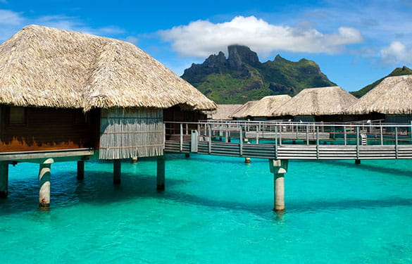 Island huts over clear blue water