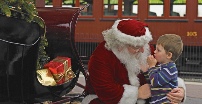 santa with child in front of train