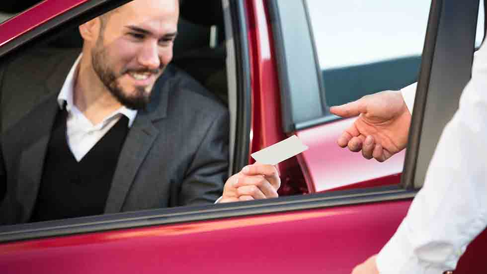 Valet Giving Receipt To Businessperson Sitting Inside Car