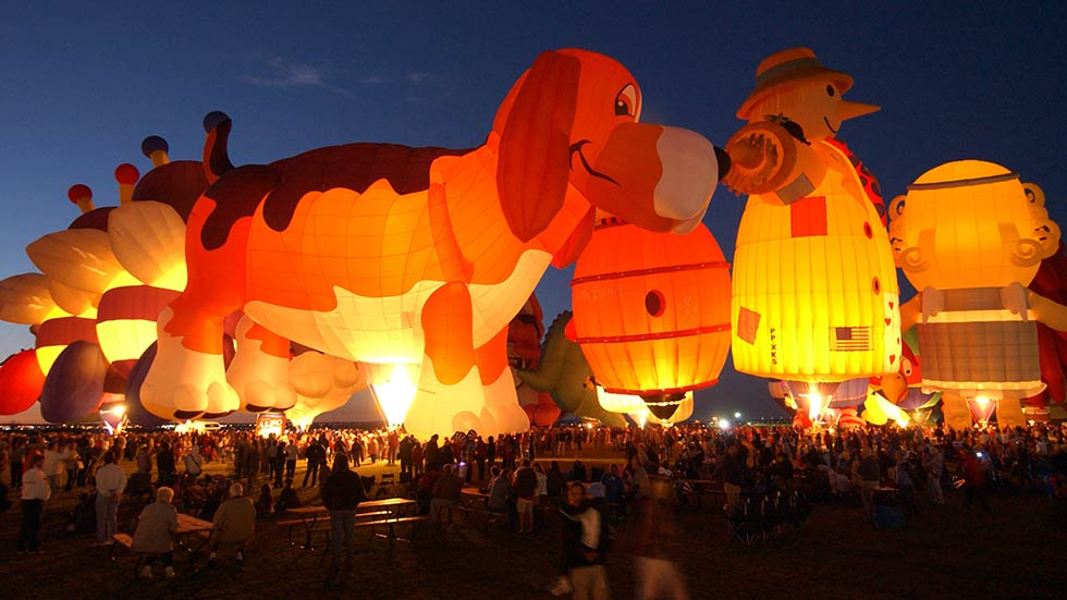 Hot air balloons illuminating The Albuquerque Balloon Festival at night.